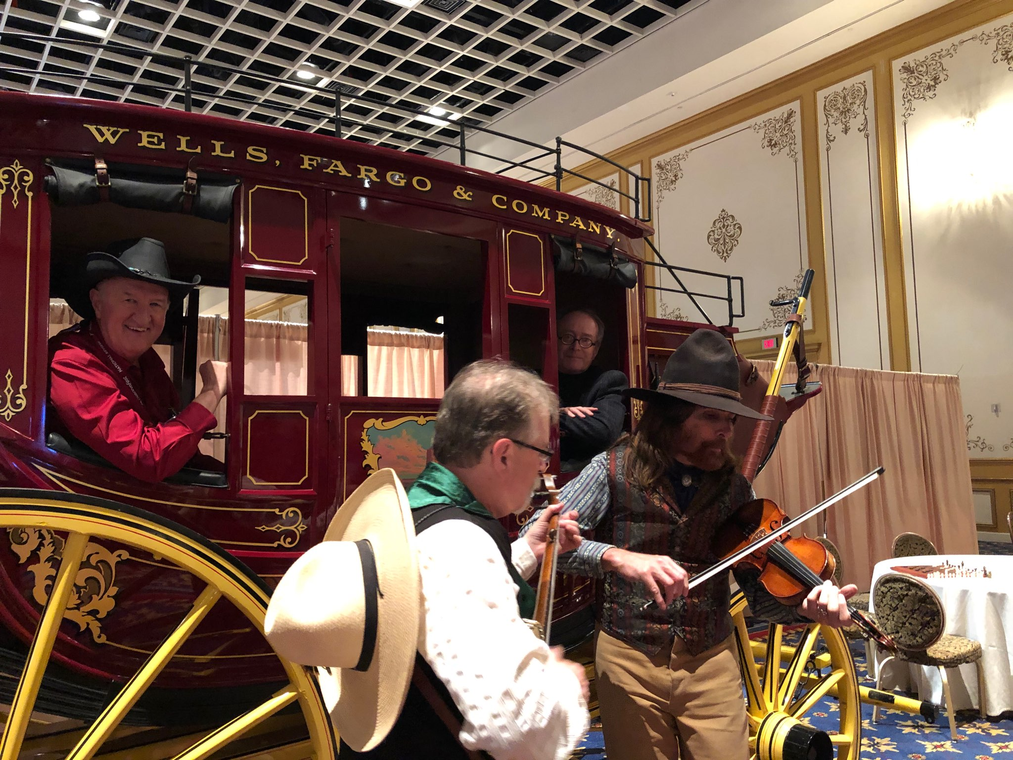 FreedomFest producer Mark Skousen and author Marc Beauchamp climb aboard the Wells Fargo wagon as Mark Gardner and Rideout entertain with western songs.